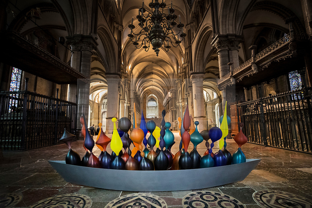 © Licensed to London News Pictures. 24/05/2018. Canterbury, UK.  Baldwin & Guggisberg's glass and steel sculpture 'Pilgrim's Boat, 2018' is displayed in Trinity Chapel at Canterbury Cathedral. A series of glass installations by artists Philip Baldwin and Monica Guggisberg reflecting on themes of war and remembrance, migration and refugees are going on display at the cathedral commemorating the 100th anniversary of the end of the First World War. Under an Equal Sky will take visitors on a journey that begins with the Boat of Remembrance in the Nave and ends with a glass wall of multi-coloured vessels in The Crypt . Photo credit: Peter Macdiarmid/LNP
