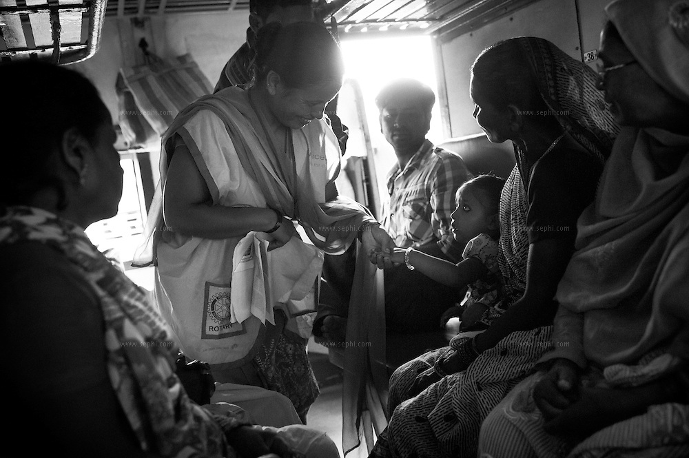 A community mobilizer at Jogbani train station examines a child on board one of the trains for the finger  marking to confirm he has been vaccinated. Transit teams are deployed at strategic locations including international borders to reach mobile and migrant populaitons.