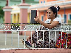 North America, Caribbean, Cuba, Remedios, teen talking on mobile phone in plaza