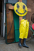 Second hand and junk store near Brick Lane in East London, UK. Outside the shop a yellow smiley face has been matched with a pair of waterproof trousers on the bottom half of a showroom dummy, in an amusing juxtapositionas if crucified, nailed to a wooden cross.