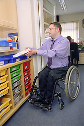Man with disability; who is wheelchair user; filing paperwork,