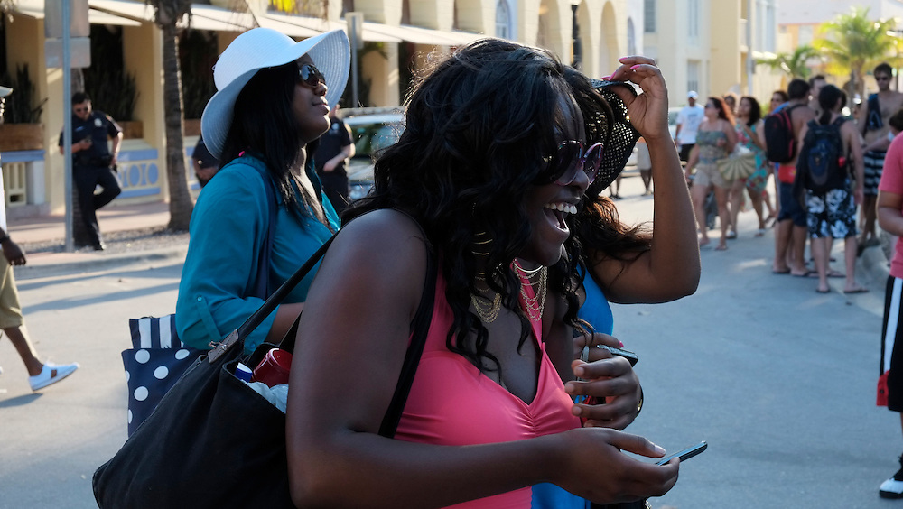 MIAMI BEACH - MAY 25: Woman laughing in the street during the Urban Beach Weekend, on May 25, 2013 in Miami Beach. This is the largest Urban Festival in the World, that caters towards the Hip Hop Generation. Over 300.000 participants make the annual trek to South Beach for 4 days full of fun, food, festivities, entertainment, music, and more.
