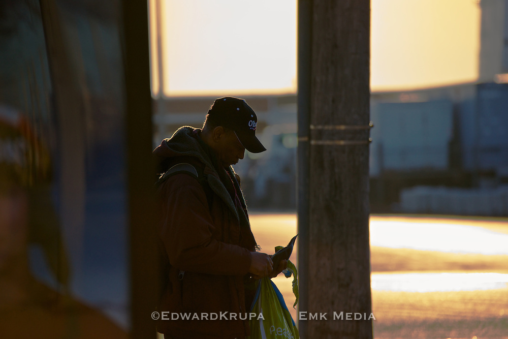 Man wearing an Obama cap waits for a bus while checking his wallet.