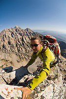 A young woman climbs the east ridge of Buck Mountain in Grand Teton National Park, Jackson Hole, Wyoming.