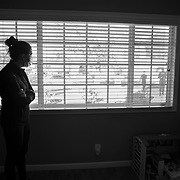 Almost 10 months since her life was thrown in turmoil by the coronavirus in March, 2020, Erin is selling her home and moving into a new home with her boyfriend. It's bitter sweet but she's looking forward to a new chapter in life, she said. Erin watches her agent and photographer at work through a window.