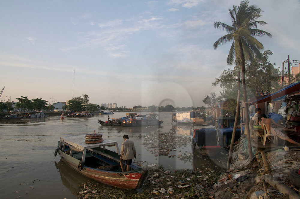 Life along the river in Ho Chi Minh city, Vietnam, Asia. Boats sailing on the polluted waters