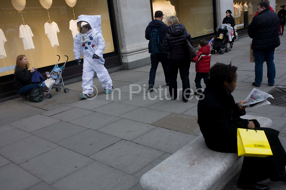 London 8/1/13: A man dressed as a NASA moon walking astronaut walks along Oxford Street outside the Selfridges department store in central London. Shoppers and passers-by seem oblivious to this symbol of 20th century American technology, now reduced to a PR stunt for the Lynx aftershave brand hosted by Selfridges. Selfridges, also known as Selfridges & Co, is a chain of high end department stores in the United Kingdom. It was founded by Harry Gordon Selfridge. The flagship store in London's Oxford Street is the second largest shop in the UK (after Harrods) and opened 15 March 1909