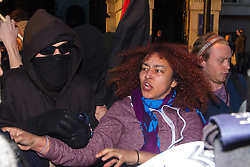 London, March 7th 2015. Following the Climate march through London, masked anarchists and environmental activists clash with police following a breakaway protest at Shell House. PICTURED: A woman shouts at TSG police officers as scuffles between Territorial Support Group officers and anarchists ensue.