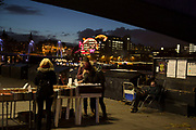 People at the second hand book stalls on the riverside walkway as dusk turns to evening on the Southbank, London, United Kingdom. The South Bank is a significant arts and entertainment district, and home to an endless list of activities for Londoners, visitors and tourists alike.
