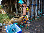 28 MARCH 2018 - BAN LAEM, PHETCHABURI, THAILAND:  A worker cools himself with water after bringing baskets of salt to a warehouse during the 2018 salt harvest in Petchaburi province, about two hours south of Bangkok. Sea salt is made in provinces south of Bangkok by flooding fields with ocean water after the rainy season. As the fields dry out from evaporation, workers go into the fields and gather the salt left behind.      PHOTO BY JACK KURTZ
