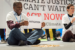 """11 December 2019, Madrid, Spain: ACT Alliance, Lutheran World Federation and World Council of Churches participants at COP25 illustrate the lack of balance in finance of the global climate response, where most ofthe finance is put into mitigation, some into adaptation, but very little into loss and damage, even though 'that's where the people are'. 'What do we want? Climate justice. When do we want it? Now!"""" they chanted."""