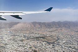 Cropped image of airplane flying above city, Maskat, Oman