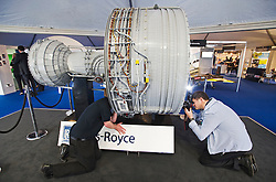 © London News Pictures. 09/07/2012. Farnborough, UK. A photographer poses a Rolls Royce inside a giant Rolls Royce engine made 152,000 pieces of Lego on day one of the Farnborough International Airshow, in Farnborough, Hampshire, UK on July 9, 2012. FIA is a seven-day international trade fair for the aerospace industry which is held every two years at Farnborough Airport . Photo credit: Ben Cawthra/LNP.