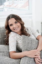 Portrait of smiling young woman sitting on couch at home
