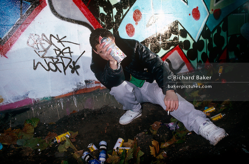 A masked youth is seen after spraying graffiti art on to a wall in the Notting Hill area of West London, England.