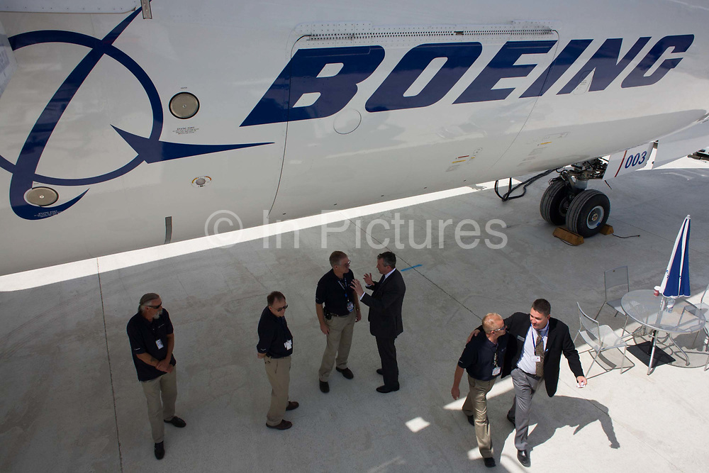 Boeing employees beneath company 787 Dreamliner (N787BX) at the Farnborough Airshow. On its first flight outside of the US during its testing programme, the newest airliner in the Boeing aviation family, has arrived at the air show for a few days of exhibitions to the aerospace-buying community and the trade press. Later the public will have the chance to see this jet up close too. The Boeing 787 Dreamliner is a long range, mid-sized, wide-body, twin-engine  jet airliner developed by Boeing Commercial Airplanes. It seats 210 to 330 passengers, depending on variant. Boeing states that it is the company's most fuel-efficient airliner and the world's first major airliner to use composite materials for most of its construction