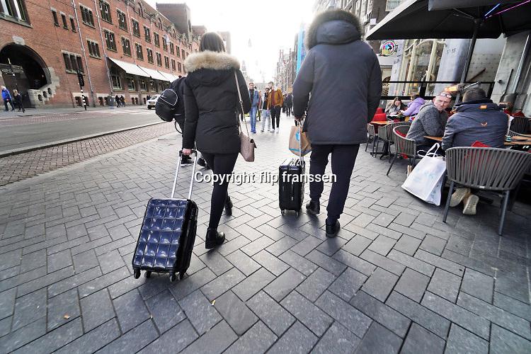 Nederland, the Netherlands, Amsterdam, 5-3-2019Twee toeristen, mannen, lopen met hun koffers vanaf het centraal station over het damrak richting de dam . Foto: Flip Franssen