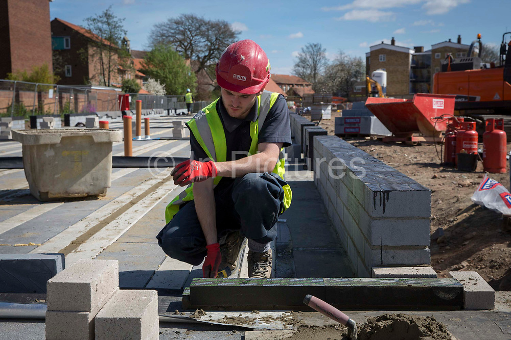 A builder using a section of Foamglas Perinsul HL for thermal insulation in the foundations of a new house on a home building construction site in Norwich. Norfolk. United Kingdom.