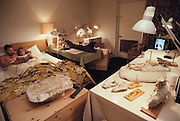 Dan Ulmer and wife, two fossil merchants share their motel room with a variety of large fossils. On the table next to the bed is a leg bone from a dinosaur and the skull of a prehistoric rhinoceros-like animal (Brontotherium sp.). Brontotherium was a genus of mammals that lived in the Lower Oligocene period about 35 million years ago in what is now North America. This photo was taken during the Fossil Fair at Tucson, Arizona, where amateur and commercial fossil collectors gather to trade in the remains of prehistoric animals. Although frowned upon by many academics, amateur collectors frequently find remains of new fossil species or very fine examples of known species. MODEL RELEASED (1991)