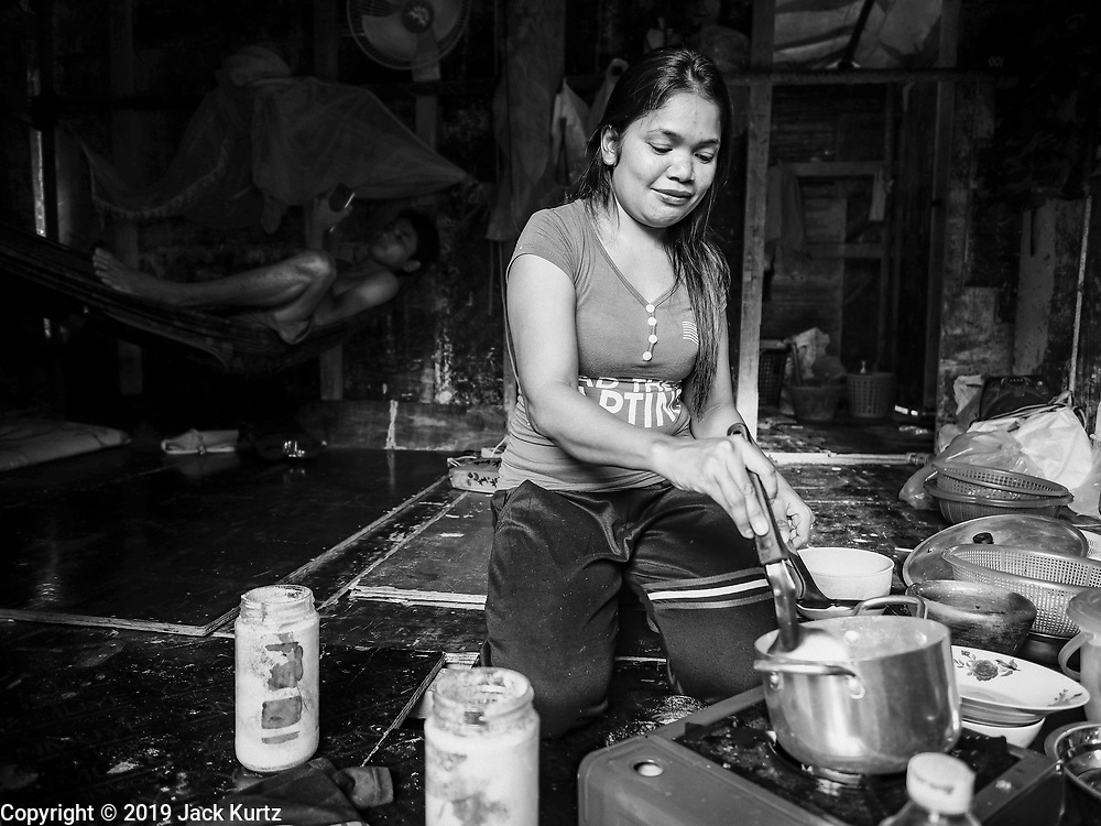 "12 FEBRUARY 2019 - SIHANOUKVILLE, CAMBODIA:  The wife of a Cambodian construction worker (in hammock in the background) makes dinner in their home in the Blue Bay casino and resort, a Chinese project in Sihanoukville. There are about 50 Chinese casinos and resort hotels either open or under construction in Sihanoukville. The casinos are changing the city, once a sleepy port on Southeast Asia's ""backpacker trail"" into a booming city. The change is coming with a cost though. Many Cambodian residents of Sihanoukville  have lost their homes to make way for the casinos and the jobs are going to Chinese workers, brought in to build casinos and work in the casinos.     PHOTO BY JACK KURTZ"
