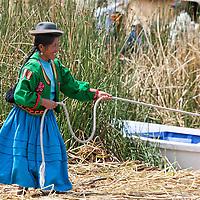 "Uros woman tying a boat on the floating Island ""Isla Uros Gaviota""."
