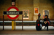A lady musician is seated at Barbican underground station in central London. The platform is actually above ground and the woman sits patiently awaiting the next train to arrive. her musical instrument stands against her bench and she watches to her right, past the London Underground sign telling us the station's name. The Barbican is Europe's largest multi-arts and conference venue presenting a diverse range of art, music, theatre, dance, film and education events. It is also home to the London Symphony Orchestra. The Guildhall School of Music & Drama is also here - one of Europe's leading conservatoires, offering musicians, actors, stage managers and theatre technicians an inspiring environment in which to develop as artists and professionals.