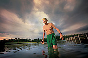 An elderly caucasian man laughs after taking a swim in a lake.