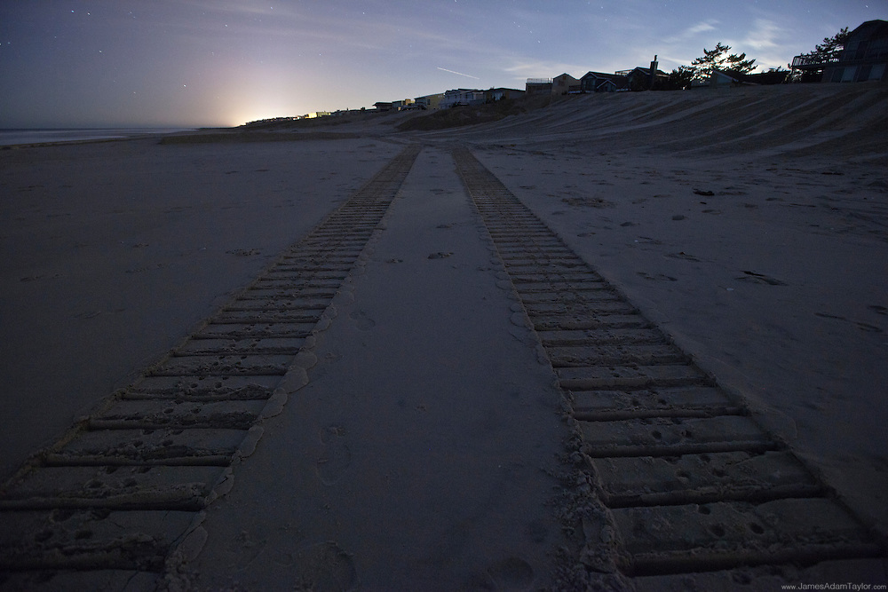 Foot prints in the sand follow a set of dozer tracks along the beach in a state of be rehabilitated after the storm.