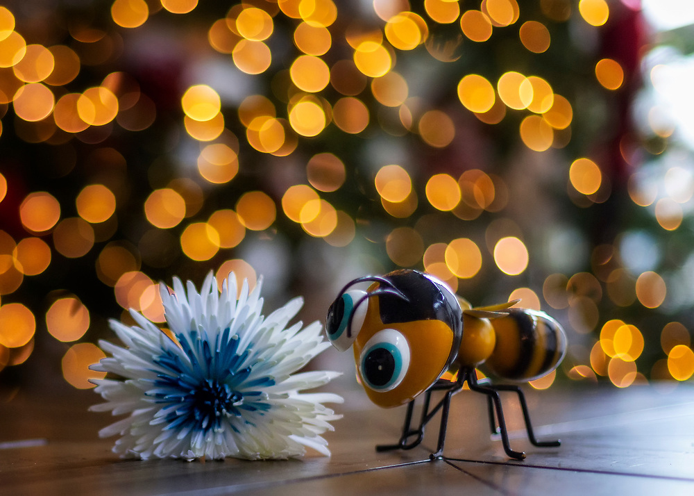 A Bee Figurine And A Flower On A Table In Front Of The Christmas Tree