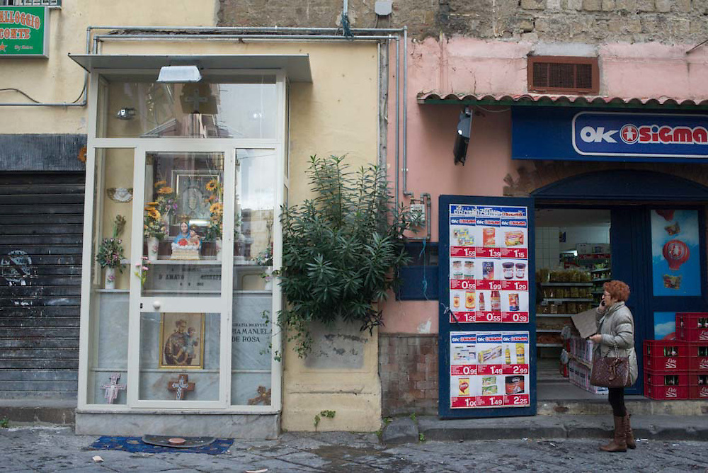 A woman talks on her cellphone outside of a store which sits next to a roadside shrine in Naples, Italy