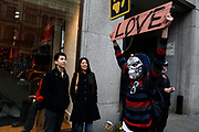 Protester wearing a silver skeleton mask holds a sign saying LOVE. Anti capitalists / anarchists go on the rampage through central London on the back of the peaceful TUC protest march. The masked demonstrators ran a twisting route through the capital confusing the police and creating a situation which was very difficult to manage. The protesters attacked banks, shops and hotels, and the police in riot gear fought  face to face with them as they were pelted with ammonia, paint and fireworks loaded with coins.