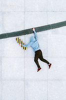 Aerial view of creative illusion of skateboarder hanging on the edge line on concrete background in Kaunas city, Lithuania.