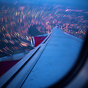 In mid-flight over Greater London, we see a passenger?s view of a turning airliner's wing and the capital's dusk landscape below at a low altitude. As the starboard (right) wing dips, the Virgin Atlantic Airbus banks and a long exposure blurs the city lights below. A small curved portion of the passenger window, red engines and the Union Jack colours are seen. As aerodynamic design, the flying machine is a perfect gesture towards the conquest of flight, copied from the characteristics of a bird?s anatomy. As art, the mere beauty of taking to the air and maintaining level, organised speed is so routine, we rarely look our from our window to marvel at how and why. Picture from the 'Plane Pictures' project, a celebration of aviation aesthetics and flying culture, 100 years after the Wright brothers first 12 seconds/120 feet powered flight at Kitty Hawk,1903. .