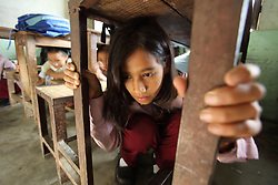 Ms Bina Burlakoti practices earthquake drill. Jana Bikash Secondary School, Matatirtha, is in the process of being rehabilitated to make the school more earthquake proof.  As part of this process children are taught how to take shelter beneath their desks in case of an earthquake. Kathmandu, Nepal.