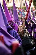 "A woman takes a selfie with the purple dressed members of ""Maria Santisima de La O"" brotherhhod"