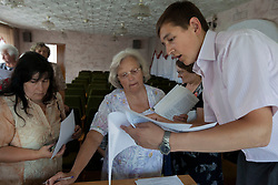 Mykola Glotov, an attorney, helps a woman during a Òspecial consultationÓ for potential clients who are children of the Second World War, Rivne, Ukraine, June 15, 2011. This vulnerable group is made up of seniors, most of whom are not receiving proper compensation as promised by the government. The legal team advises them on how to properly fill out forms and submit them to the courthouse, while encouraging them not to give up on their rights. More than half of the worldÕs population, four billion people, live outside the rule of law, with no effective title to property, access to courts or redress for official abuse. The Open Society Justice Initiative is involved in building capacity and developing pilot programs through the use of community-based advocates and paralegals in Sierra Leone, Ukraine and Indonesia. The pilot programs, which combine education with grassroots tools to provide concrete solutions to instances of injustice, help give poor people some measure of control over their lives.