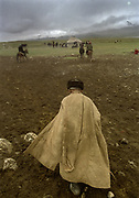 """An elderly wearing a Chapan walks toward where the wedding ceremony will take place, after a game of Buzkachi.<br /> Buzkachi (traditional afghan horse game) played in Utsch Delgha (""""three valleys"""") previous to a Kyrgyz wedding ceremony. Due to the high altitude, horses can not be bred in the Little Pamir. They are brought from the lower elevations especially Badakhshan region and the Wakhan corridor.<br /> <br /> Adventure through the Afghan Pamir mountains, among the Afghan Kyrgyz and into Pakistan's Karakoram mountains. July/August 2005. Afghanistan / Pakistan."""
