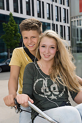 Portrait of teenage couple listening music on bicycle, smiling