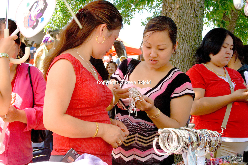 Hmong woman inspect jewelry and bling at outdoor concession stand. Hmong Sports Festival McMurray Field St Paul Minnesota USA