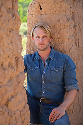 good looking blond man with blue eyes by a rustic setting