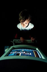 Young boy playing a computer game, England, UK.