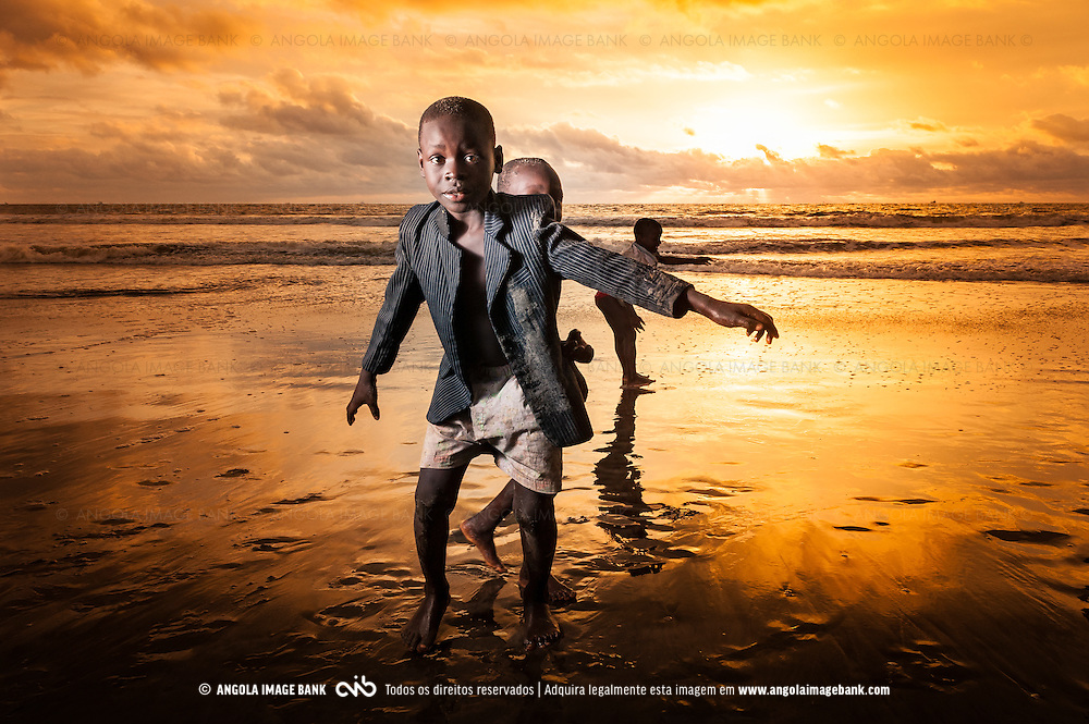 Crianças a brincarem alegres ao pôr do sol na praia de Fútila em Cabinda. Angola