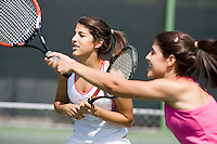 teenage and young adult sisters playing tennis doubles together