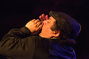 """""""Shaky"""" Dave Pollack of Alex Battles & The Whisky Rebellion playing harmonica into a vintage microphone."""