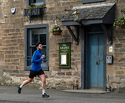 "Livingston During Coronavirus Outbreak, 21 March 2020<br /> <br /> Cafes, pubs and restaurants have been ordered to close, to tackle coronavirus. Nightclubs, theatres, cinemas, gyms and leisure centres must do so ""as soon as they reasonably can"", the government said.<br /> <br /> These steps are part of the UK's social distancing measures.<br /> <br /> Everybody is being asked to avoid non-essential contact with other people.<br /> <br /> Pictured: The Grapes pub in East Calder was locked up today as they followed the government's advice. A jogger gets some exercise during the social distancing phase<br /> <br /> Alex Todd 