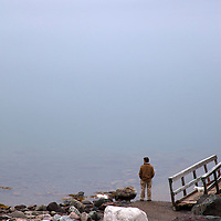 North America, Canada, Nova Scotia, Guysborough. A man stands at foggy water's edge in Guysborough.