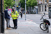 A metropolitan police officer takes down the details of a male E-scooter rider that he stopped riding on the pavement on Tooley Street, SE1 on the 25th of May 2021 in London, United Kingdom.