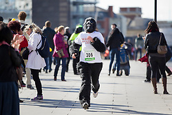 © Licensed to London News Pictures. 22/09/2012. LONDON, UK. A runner wearing a gorilla costume is seen running past members of the public on London Bridge as they take part in the 2012 Great Gorilla Run in London today (22/09/12). Now in its 10th year, the annual event sees hundreds of competitors take part in a 7km fun-run dressed as gorillas to raise money for mountain gorilla conservation projects in Africa. Photo credit: Matt Cetti-Roberts/LNP