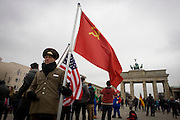 """Actors in US and Soviet army uniforms hold flags to recount German history during the second world war and later, the cold war - beneath the Brandenburg Gate in Unter den Linden in central Berlin, Germany. The site is near the former border between Communist East and West Berlin during the Cold War. Here also, Berlin was separated by the occupying sectors of US, British, French and Soviet forces after WW2. The Berlin Wall was a barrier constructed by the German Democratic Republic (GDR, East Germany) starting on 13 August 1961, that completely cut off (by land) West Berlin from surrounding East Germany and from East Berlin. The Eastern Bloc claimed that the wall was erected to protect its population from fascist elements conspiring to prevent the """"will of the people"""" in building a socialist state in East Germany."""