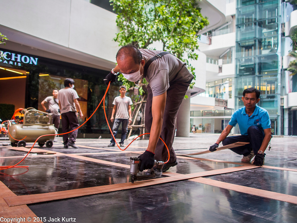 """27 MARCH 2015 - BANGKOK, THAILAND:  Construction workers install flooring on during the grand opening of """"EmQuartier"""" a new mall in Bangkok. """"EmQuartier"""" is across Sukhumvit Rd from Emporium. Both malls have the same corporate owner, The Mall Group, which reportedly spent 20Billion Thai Baht (about $600 million US) on the new mall and renovating the existing Emporium. EmQuartier and Emporium have about 450,000 square meters of retail, several hotels, numerous restaurants, movie theaters and the largest man made waterfall in Southeast Asia. EmQuartier celebrated its grand opening Friday, March 27.    PHOTO BY JACK KURTZ"""
